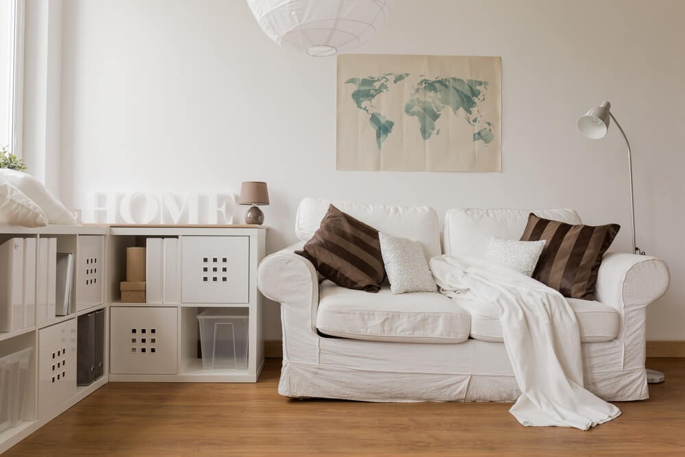Messy elegance denotes this sofa / throw pillow configuration. White sofa with brown and white throw pillows along with a white throw blanket.