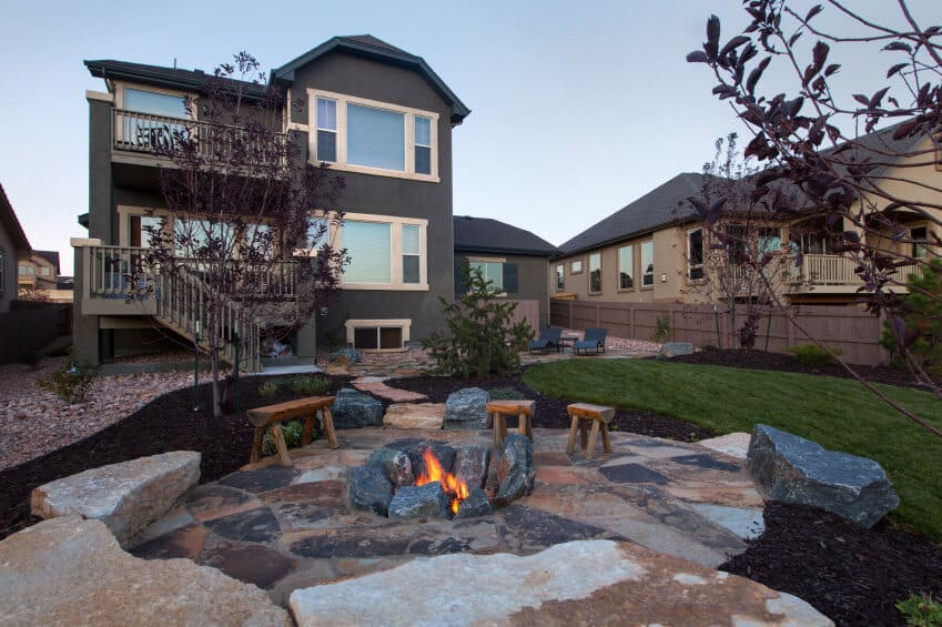 Patio fire pit dug into the ground surrounded by large rocks.