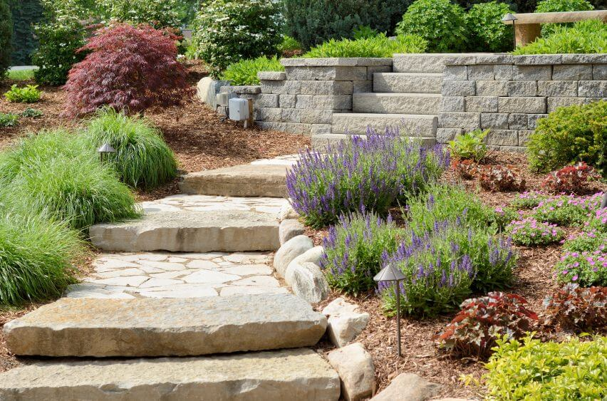 Large paving slabs and paved concrete lead to this outdoor garden, cutting through perennial flowers, Barberry, and shrubs that seem to grow in patches beside the paved stones.
