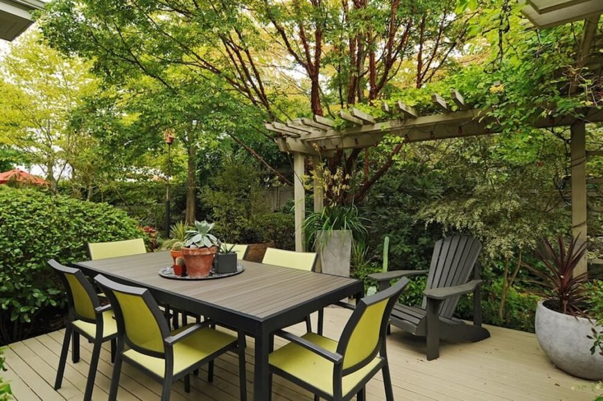In a yard flush with thick greenery, this deck provides a simple but effective open space for dining and relaxing, with plenty of room for a large dining set and adirondack chairs.