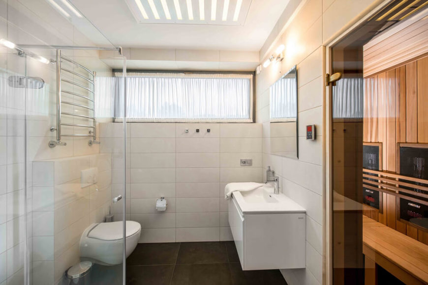 The bathroom is a bright burst of white in the home, with large format tiles wrapping the walls. The glass walk-in shower, floating vanity, and upper level window all enhance the modern look.
