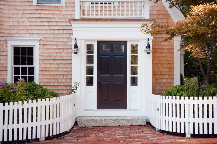 Enclosed within the white wooden fences are maple tree, greenery and flowering shrubs, playing like they will be on the loose and running through the brick pathway.