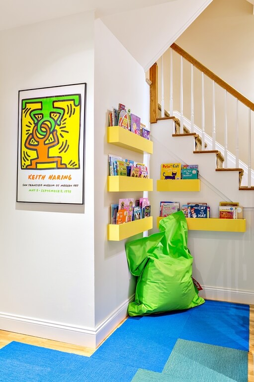 Unused space such as this corner by the stairs can be fitted into a nice reading space that is out of the way. This is an amazing way to make an unused space functional and give your children a space of their own to go and read.