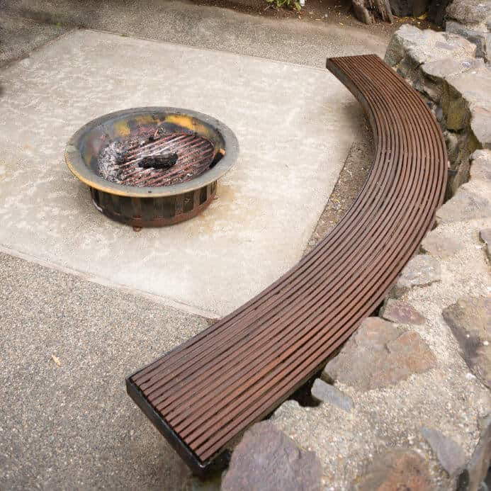 Round grate style fire pit on concrete slab patio with curved would bench seating.