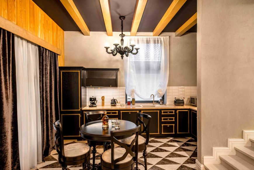 The kitchen stands out with a highly textural look, courtesy of dark cabinetry with gold highlights, a checkered floor tile design, and a black ceiling crossed with natural wood exposed beams.