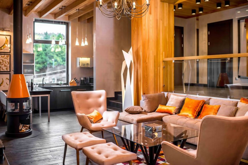 Viewed in the opposite direction, we see the kitchen area illuminated beneath a massive window. The rich hardwood flooring connects the far ends of this space and unifies the color palette.