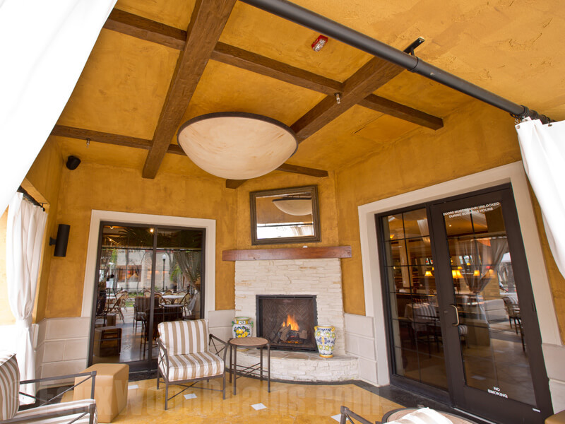 Faux beams create a tic-tac-toe board on the textured ceiling of this bold yellow sunroom. Very similar to a coffered ceiling, but much more rustic.