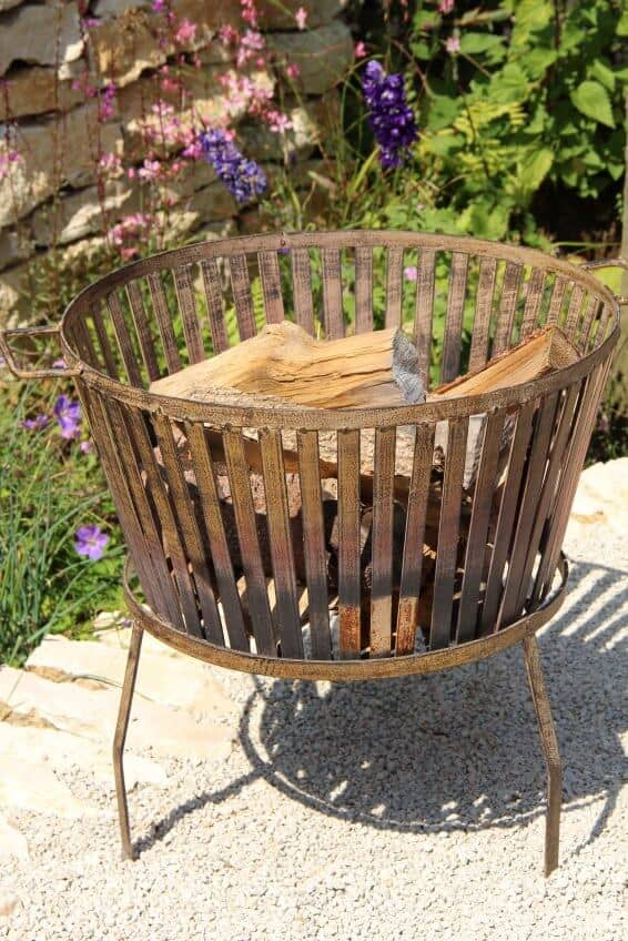 Example of a freestanding metal grate style fire pit that burns wood. This is a very simple fire burning solution for the backyard that can be easily moved.