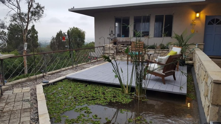 "Set right above a small manmade pond, this deck truly takes ""floating"" literally. Its light grey paint helps it stand out and the solid design makes for years of enjoyment."