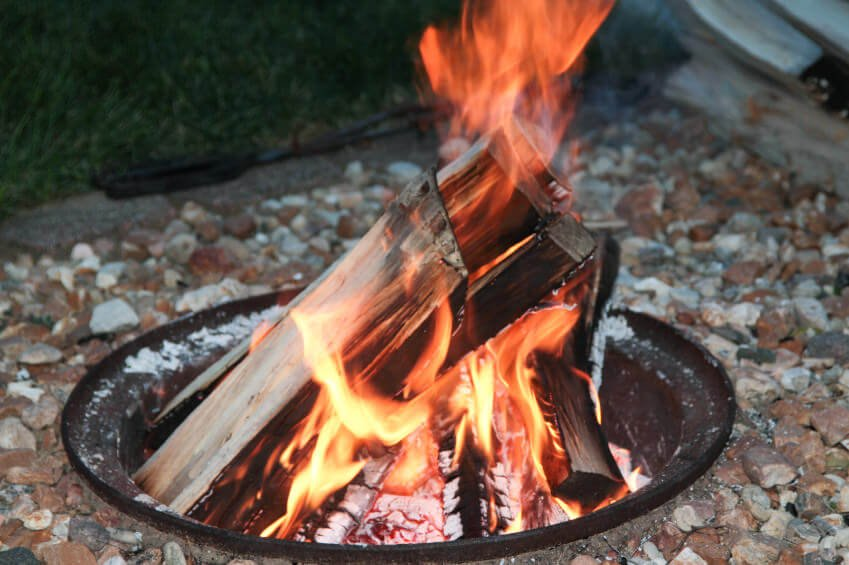 Small pit style fire pit with inverted metal dome inserted into the ground surrounded by gravel.