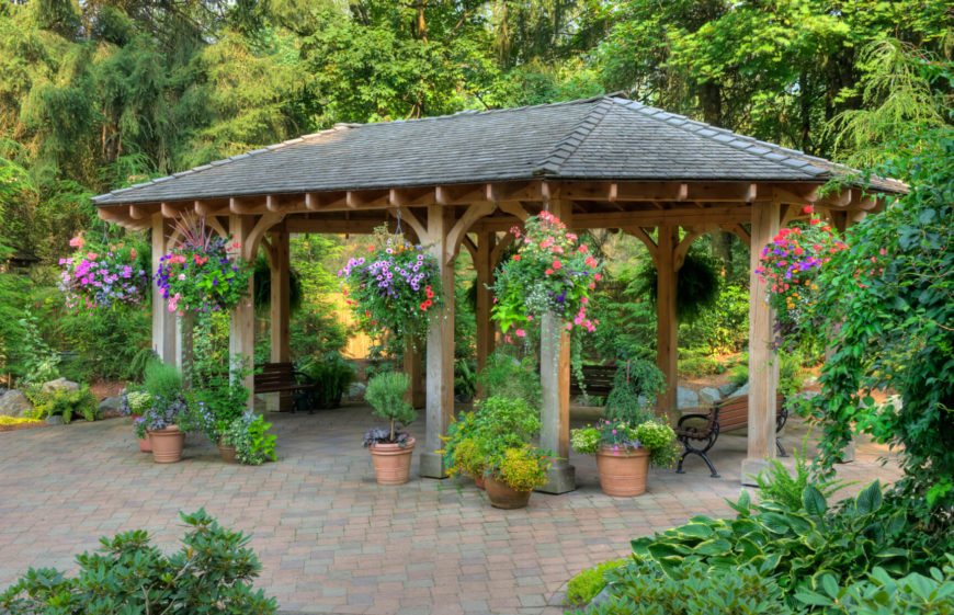 This patio gazebo houses a few benches and a number of potted plants. Gazebos work well with plants; by hanging plants from the pillars of your gazebo, you bring vibrancy and life to your structure.