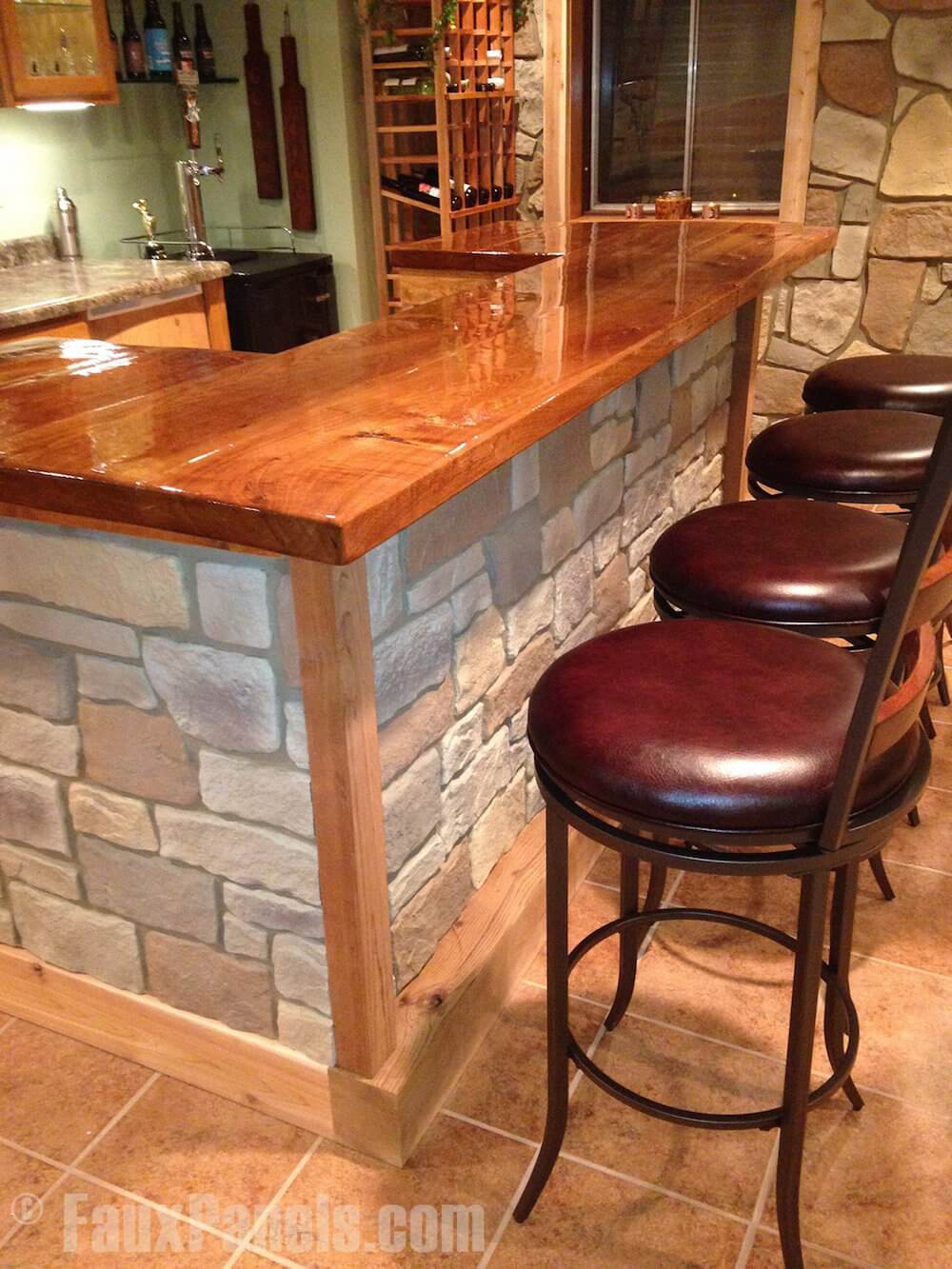 Alternatively, for a more rustic look this stacked stone facade is a perfect solution. Paired with wooden cabinetry, a butcher-block island, and plenty of wine bottle storage, the stone stands out beautifully.