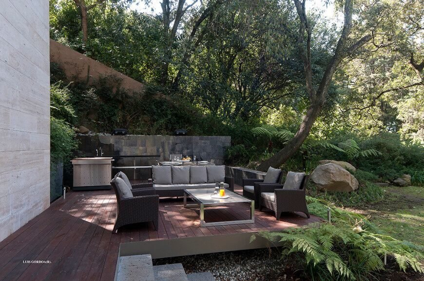 This floating deck design covers a more uneven part of the landscape, providing a tall, flat space for outdoor cooking and dining. It's bordered by the house and a small stone wall for added privacy.