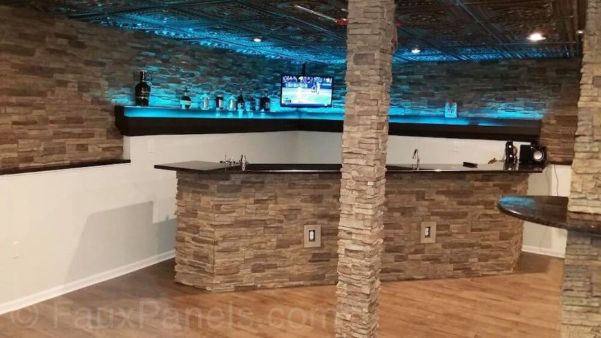 There is a wealth of faux stone in this basement home bar. The walls, the base of the island, and the support columns throughout. Blue backlighting on the shelving gives the area a polished, nightclub-like feel.