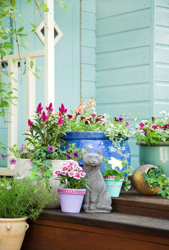 The cat figure beside the pots make the surrounding a safe haven for animals. The over-large and medium sized ceramic pots make it more appealing with the bluish and greenish colors. Plus, the colorful blossoms and the wooden steps make it more natural and cool.