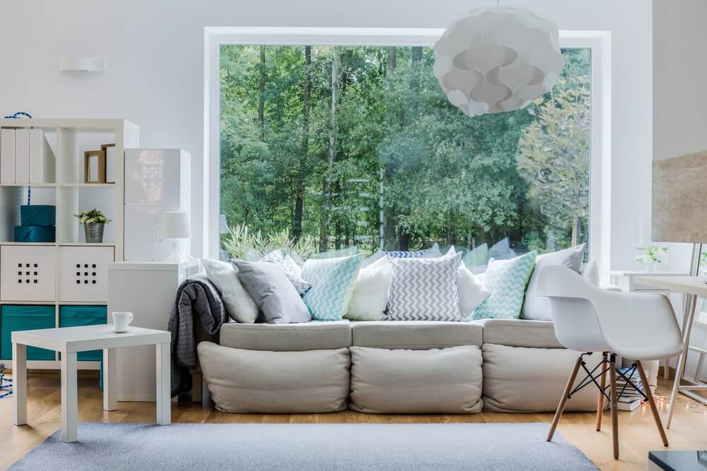Grey sofa loaded with light blue, white and grey pillows - a mix of solid and geometric striped pillows.