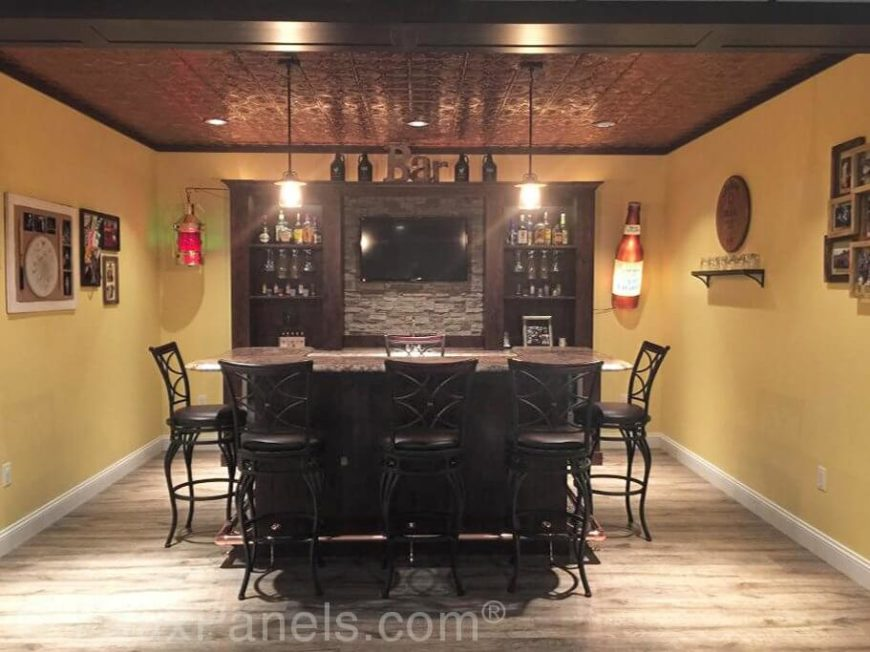 While the stone in this spacious home bar has been greatly toned down, it provides a comfortable contrast from the rich, dark wood cabinetry and the yellow walls.