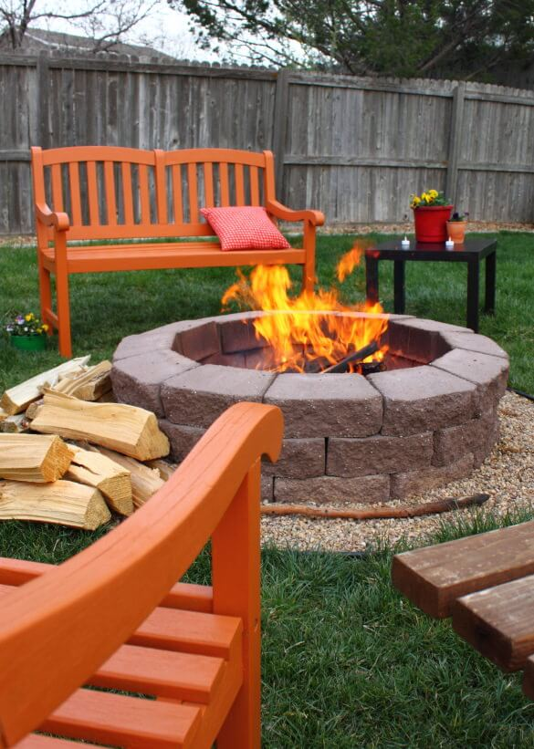 Round brick fire pit surrounded by a row of tiny gravel built in the middle of the grass in the backyard.