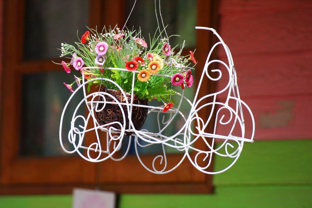 A cute wire sculpture serving as the container for a small flower bouquet in a small wicker basket.