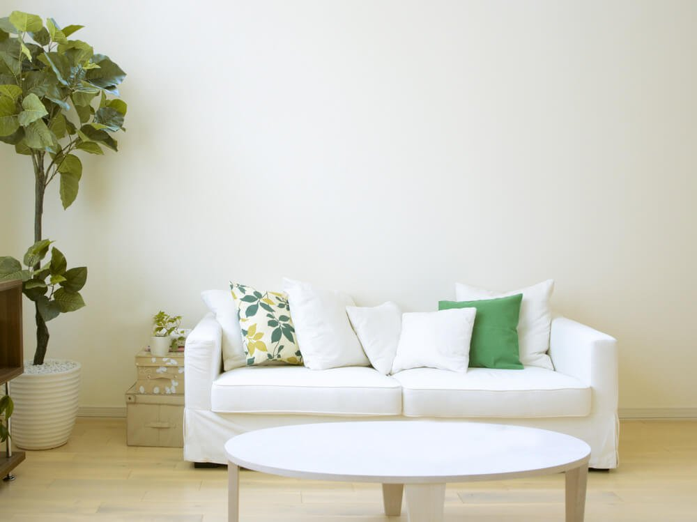White couch with one floral pillow, 5 solid white pillows and one solid green pillow.