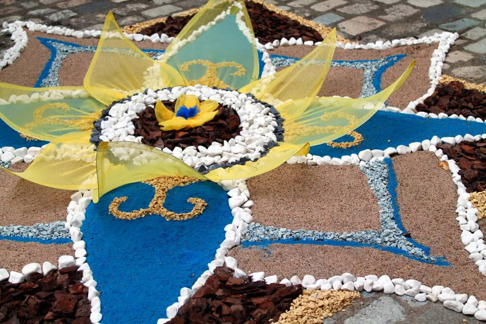 Patio mosaic with small flower in the center.