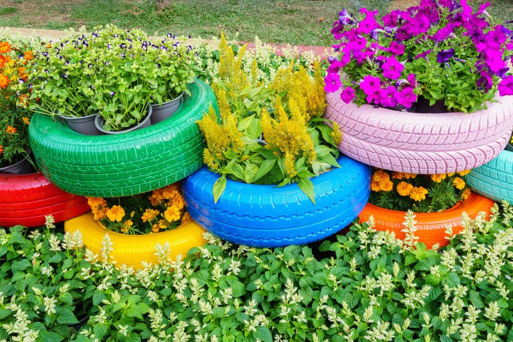 3 rows of colorfully painted tires stacked on top of one another to create a multi-level tire planter garden set in among plants.