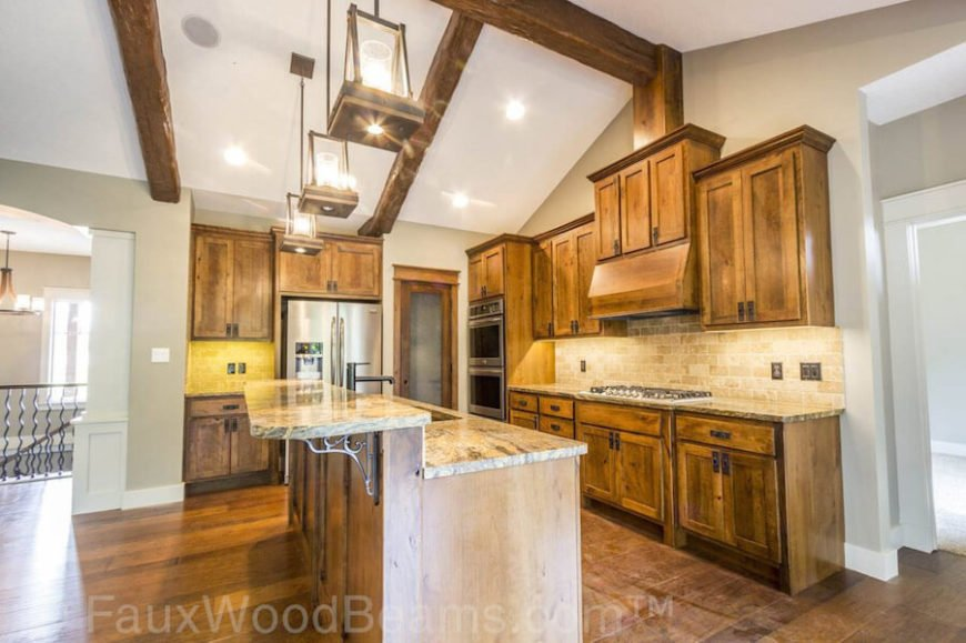 Warm wood tones, granite countertops, and rustic light fixtures are the perfect accompaniments to the stunning, heavily textured rustic faux wooden beams running across the vaulted kitchen ceiling.