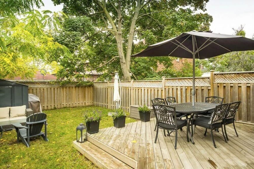 Square designs are the most common floating deck shape, and they lend themselves well to a variety of spaces. Tucked into the corner of a yard, this light colored deck meshes with the fence design well.