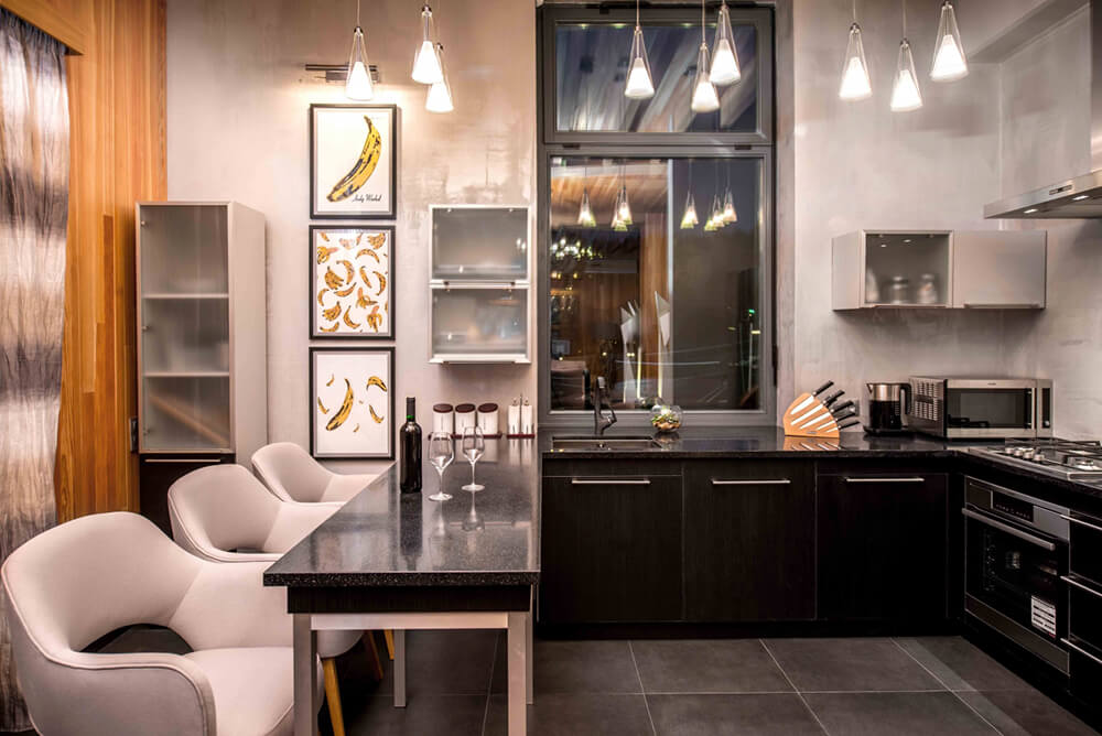 The kitchen contrasts from the rest of the open area, with dark tile flooring, black cabinetry, and light grey walls. Upper cupboards feature glass doors for a striking contemporary look.