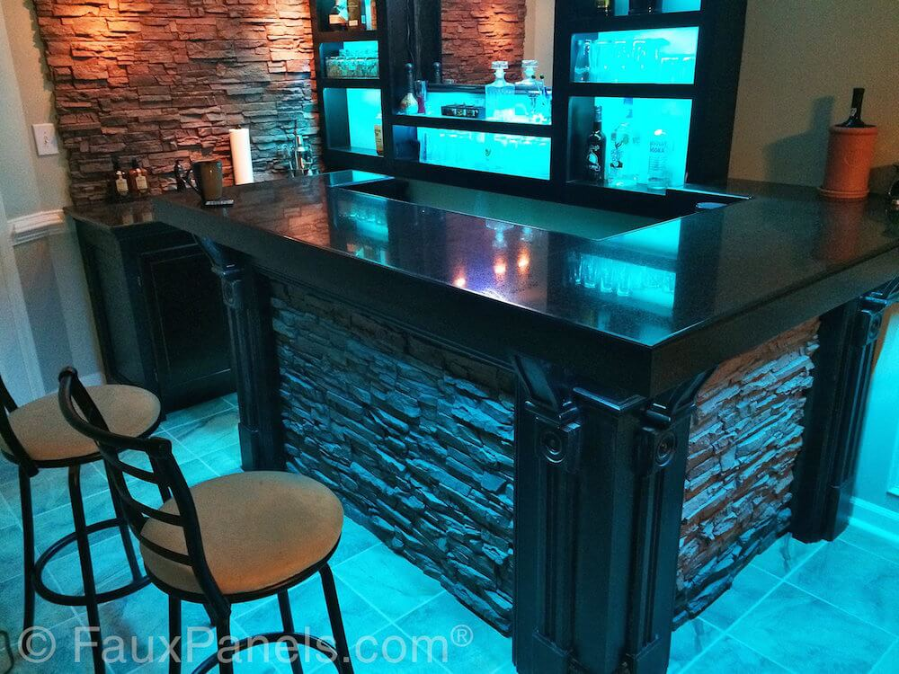 Again, blue light is used to highlight stonework and glass in a contemporary home bar area. Faux stone is used both on the walls and on the base of the bar.