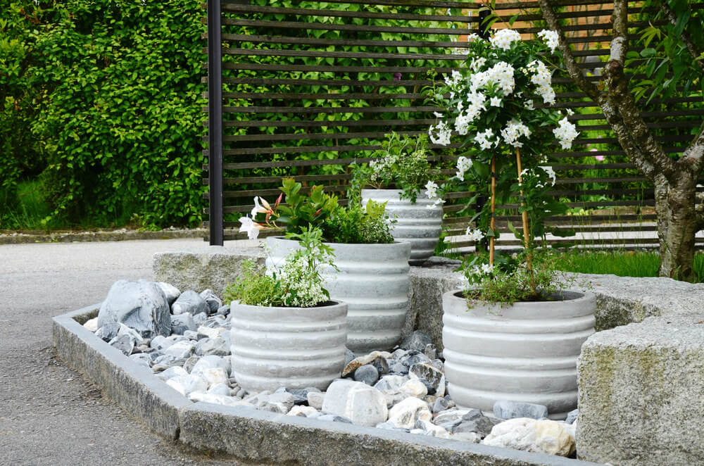 I love these cement barrel plant and flower pots inside a large rock garden on the edge of a large patio