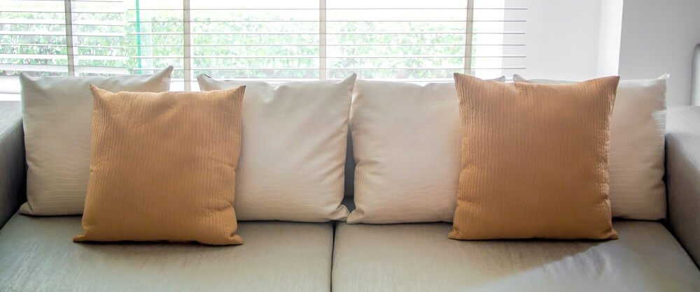 Sofa with throw pillows lined along the back with 2 brown pillows on top for a symmetric throw pillow design.