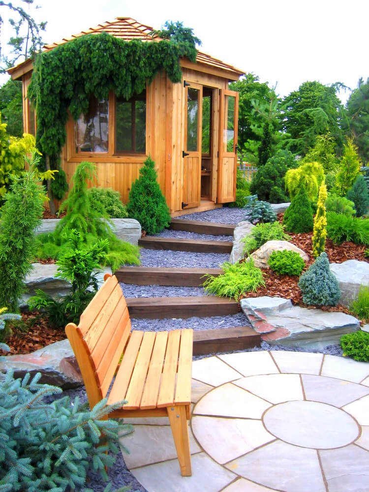 A pebbled pathway separated by layers of wooden steps that's lined with landscaped shrubs on the sides will lead you from the isolated wooden bench at the paved concrete flagstone to the inviting doors of the wooden gazebo at the top.