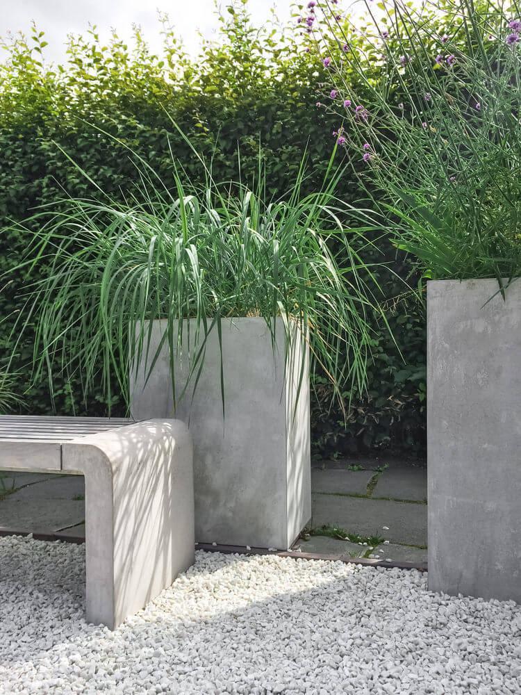 Tall modern cement planter holding tall grass on a patio.