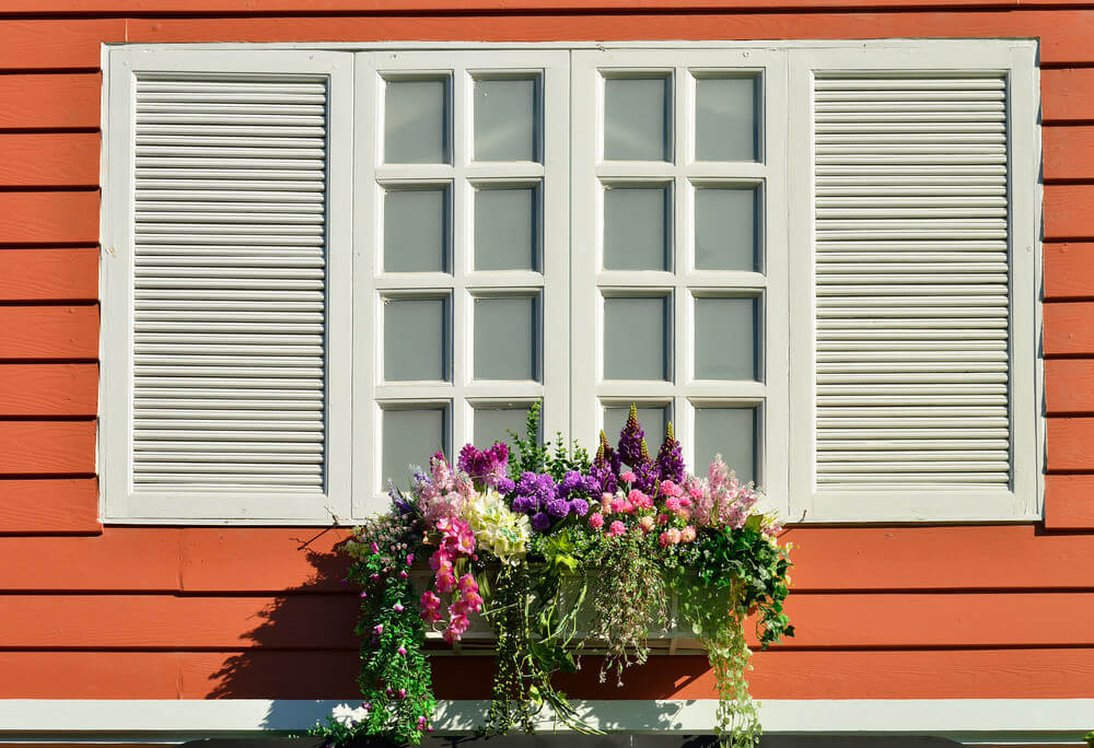 Small window flower box with a variety of flowers creating a miniature garden effect.