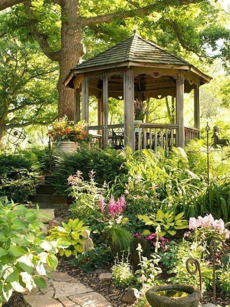 Up a stone path and in the woods is this wooden gazebo surrounded by greenery. This small gazebo is a beautiful shady and relaxed spot to host an intimate meal or even just relax and read a book.