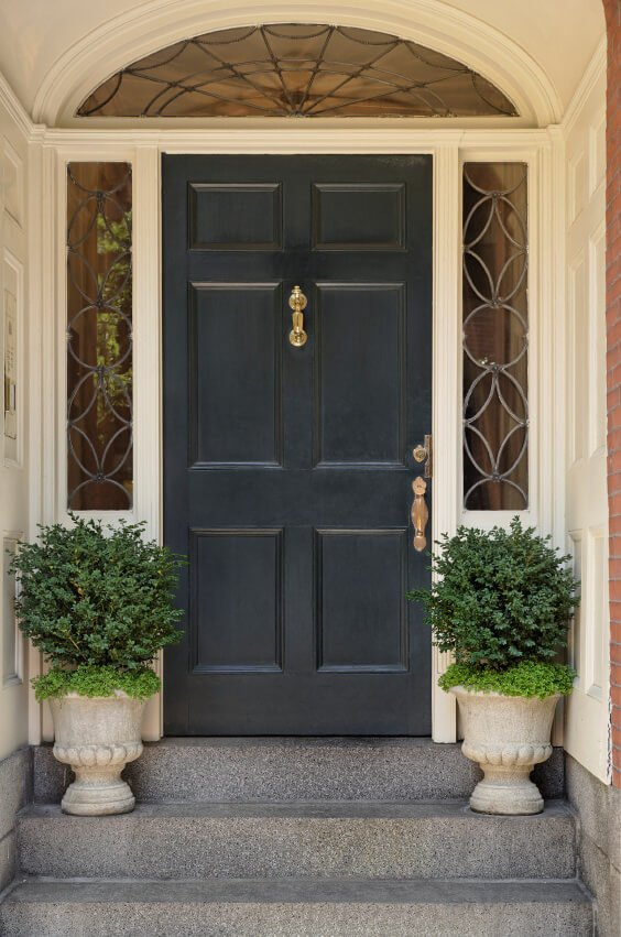 Green shrubs in gothic pots inspire this front door.