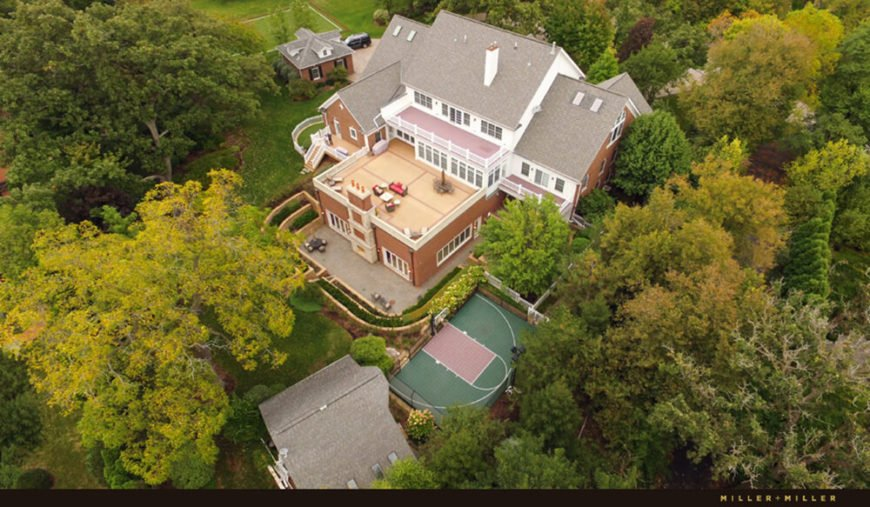 Pulling back to an aerial view of the property, we see the pool house structure at center, topped with an expansive rooftop patio.