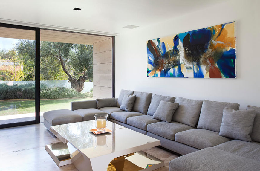 This living room has space for many people and is a cozy and inviting spot for guests to hang out and relax. The modern table and simple lighting in this room makes for an open and modern feel.
