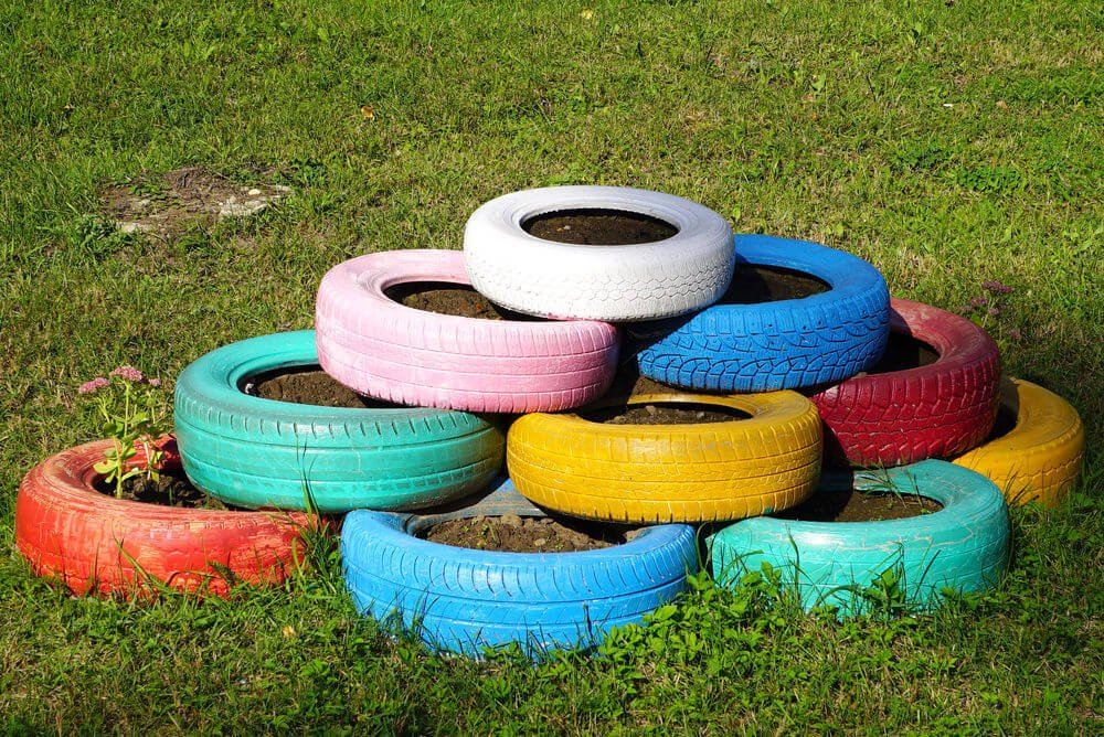 The beginnings of a colorful tire garden with a series of painted tires stacked on top of on another in a staggered formation.