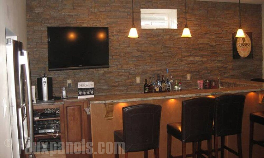 The entire back wall of this man cave's bar area is paneled with faux stones. The difference in coloration and texture draws the eye right to the bar area.