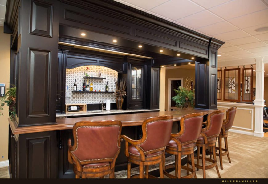 The luxuriously styled full bar offers rich wood seating, dark cabinetry, and a vast bar top space for interacting with guests and friends. Tucked into an open area near the kitchen, pool, and home gym, it's a great social hub.