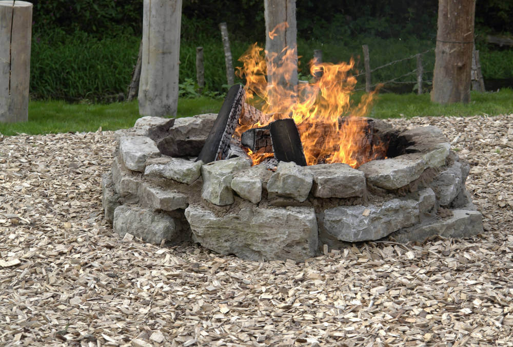 Backyard fire pit aid from large rocks placed in a circle. Perfect for burning large pieces of wood.