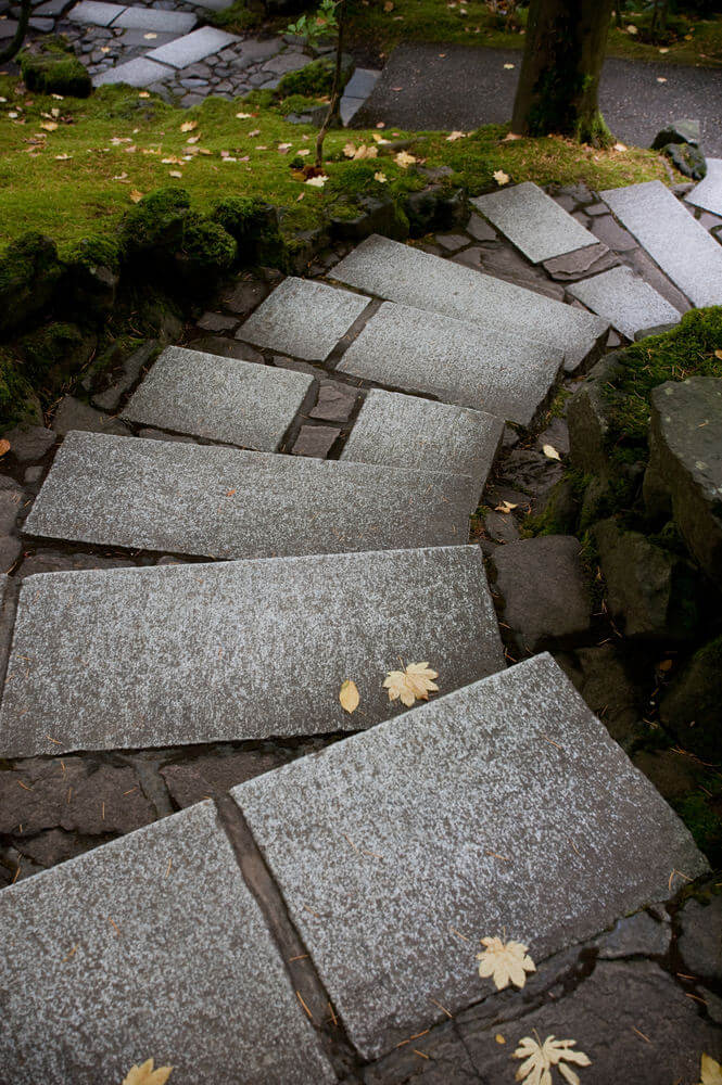 Smooth paving slabs with occasional appearances of broken concrete turn in bending directions and are side by side with well-trimmed green grass set apart by boulders.