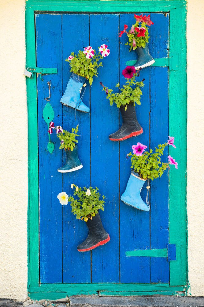 A brightly painted wooden door is decorated with three pairs of gumboots that match harmoniously with the door's colors. These gumboots are used as door mounted planters with colorful flowers that provide a rich playful contrast to the door's ocean hues.