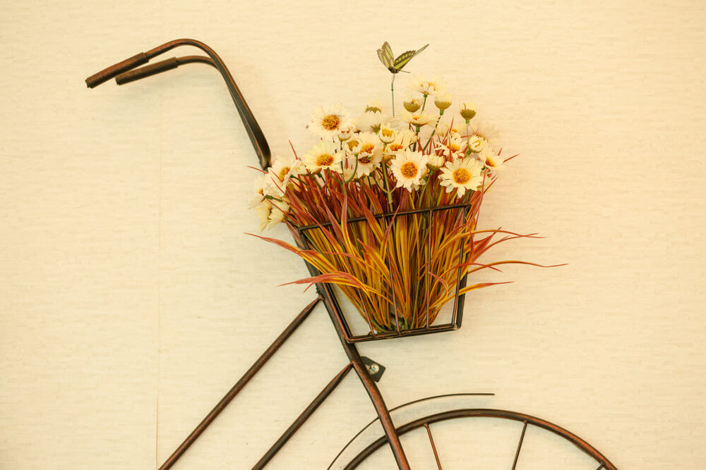 Here's a flower holder against a wall with a bike outline on the wall.