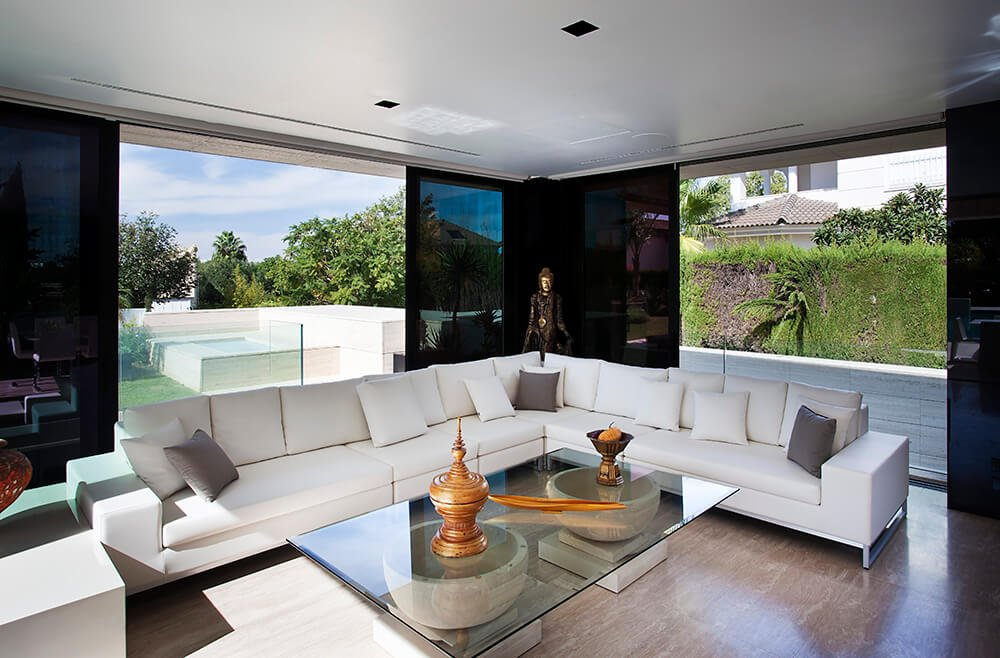 Starting in the upper-level living room, we see the startling high contrast look that combines sleek black glass, bright stone, and detailed furnishings.