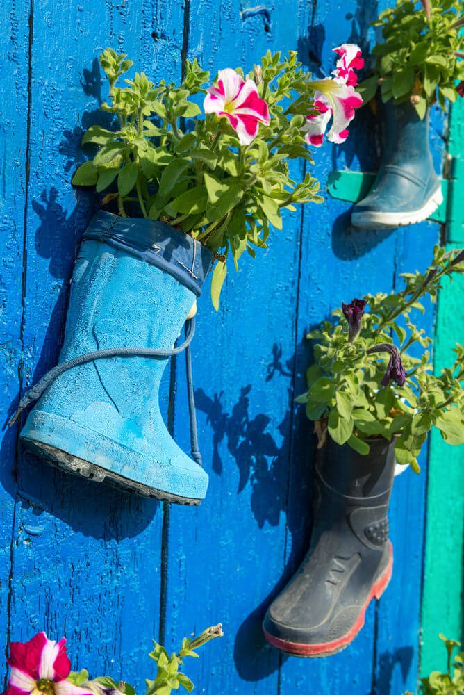 A trio of gumboots fixed onto a blue-painted wooden door are used as flower planters. The richness of colors in this area alone would be a pleasant feast to the eyes.