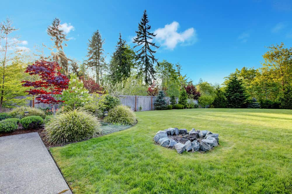 Example of an attractive easy DIY backyard fire pit in the middle of an expansive lawn built with large rocks placed in a circle.