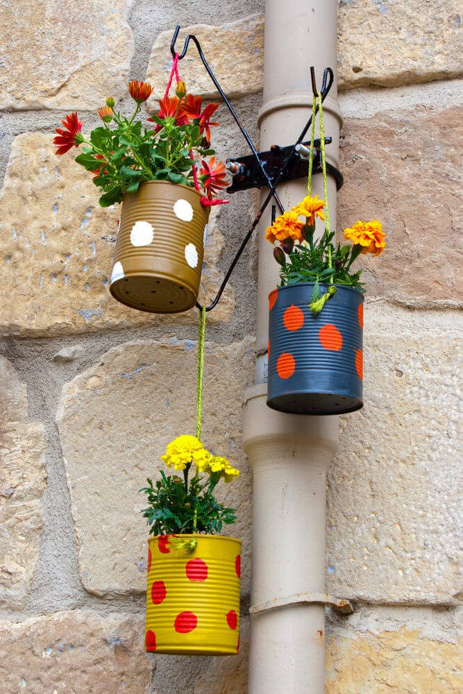 Picture of small flower bouquets planted in tin cans that are painted.